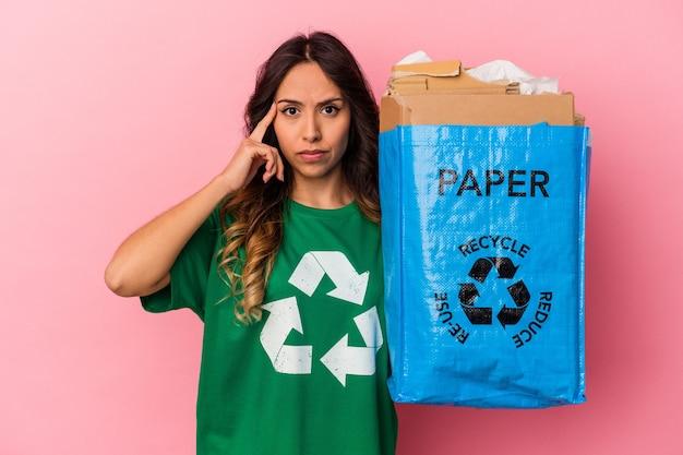 Jovem mulher mexicana, reciclando papelão isolado no fundo rosa, apontando o templo com o dedo, pensando, focado em uma tarefa.
