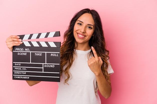 Jovem mulher mexicana segurando claquete isolada no fundo rosa, apontando com o dedo para você como se fosse um convite para se aproximar.
