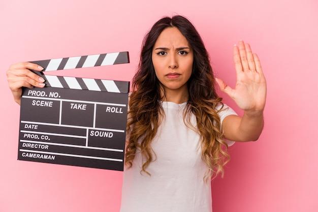 Jovem mulher mexicana segurando claquete isolada no fundo rosa em pé com a mão estendida, mostrando o sinal de stop, impedindo-o.
