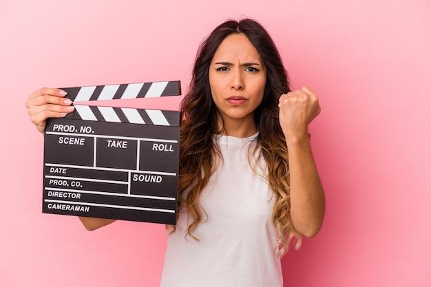 Jovem mulher mexicana segurando claquete isolada no fundo rosa, mostrando o punho para a câmera, expressão facial agressiva.
