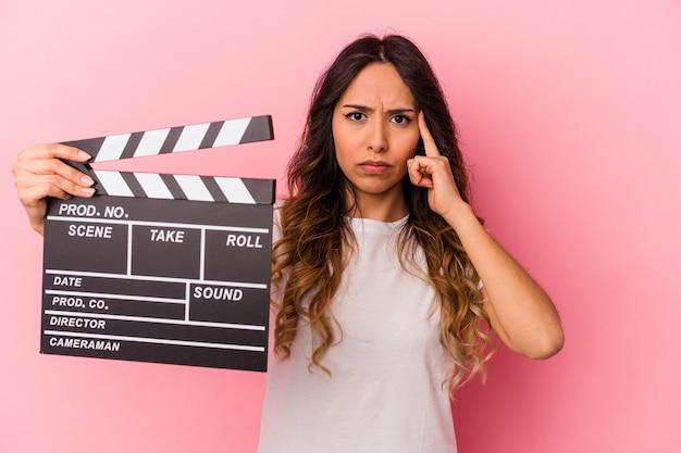 Jovem mulher mexicana segurando claquete isolada no templo apontando de fundo rosa com o dedo, pensando, focada em uma tarefa.