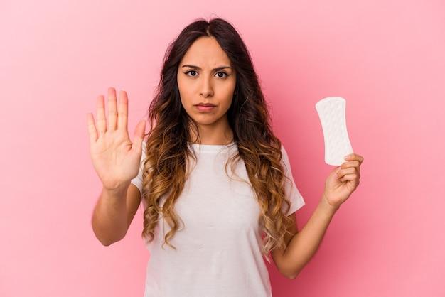Jovem mulher mexicana segurando uma compressa isolada em um fundo rosa em pé com a mão estendida, mostrando o sinal de stop, impedindo você.