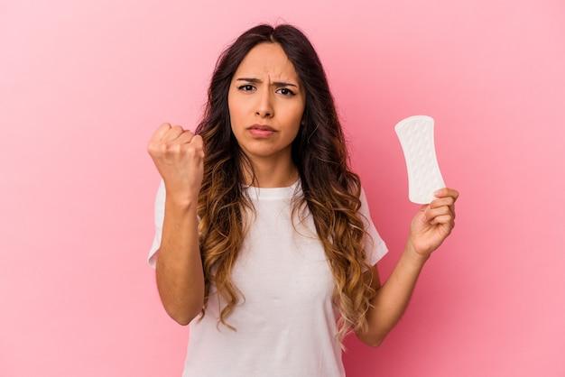 Jovem mulher mexicana segurando uma compressa isolada no fundo rosa, mostrando o punho para a câmera, expressão facial agressiva. Foto Premium