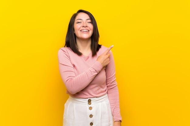 Jovem mulher mexicana sobre amarelo isolado apontando para o lado para apresentar um produto