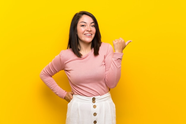 Jovem mulher mexicana sobre fundo amarelo isolado, apontando para o lado para apresentar um produto