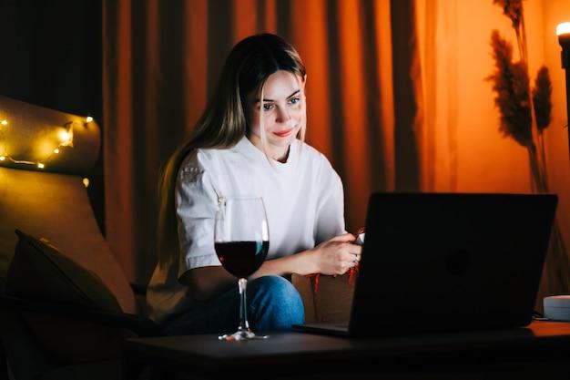 Jovem mulher milenar com videochamada no laptop e bebendo vinho, usa a tecnologia para se comunicar com amigos ou família.