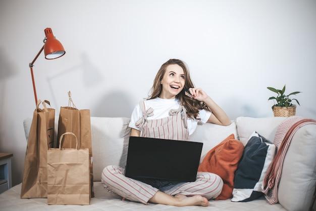 Jovem mulher milenar, compras online em casa. pessoa do sexo feminino usando laptop e cartão de crédito para comprar coisas novas.