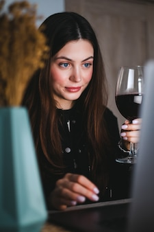 Jovem mulher milenar fazendo videochamada no laptop e bebendo vinho, usa a tecnologia para se comunicar com amigos ou familiares