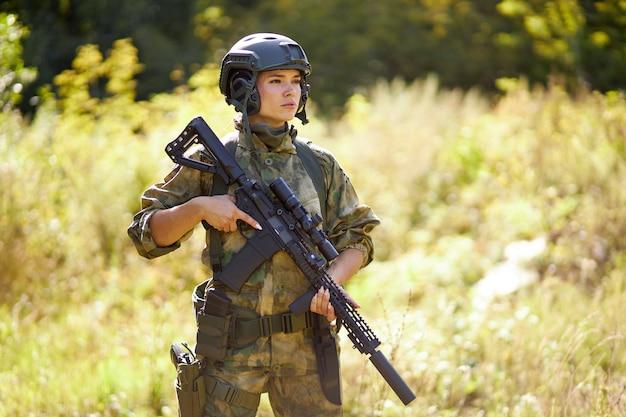 Jovem mulher militar caucasiana tem uma arma na mão na natureza, ela vai caçar, caçar na floresta é um hobby. jogo com armas