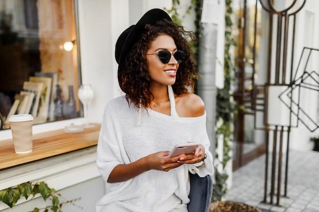 Jovem mulher misturada com penteado afro, falando pelo telefone móvel e sorrindo em meio urbano. garota negra vestindo roupas casuais. segurando a xícara de café. chapéu preto.
