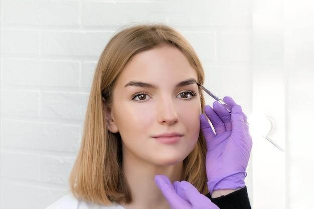 Jovem mulher modelando as sobrancelhas com pincel, close-up