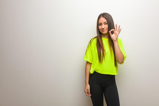 Jovem mulher moderna alegre e confiante fazendo o gesto de ok