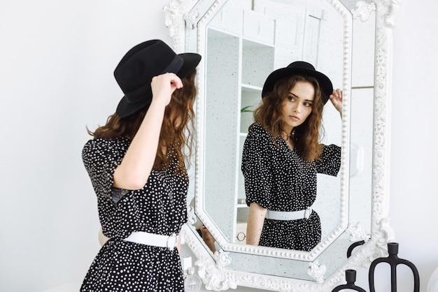 Jovem mulher moderna com chapéu e vestido se olha no espelho