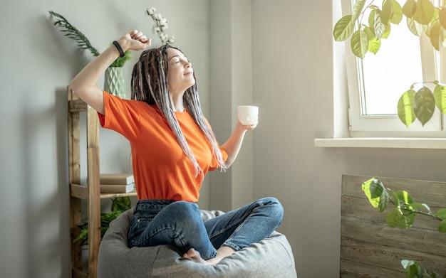 Jovem mulher moderna com uma xícara de café está sentada em uma espreguiçadeira ao lado da janela e se espreguiçando