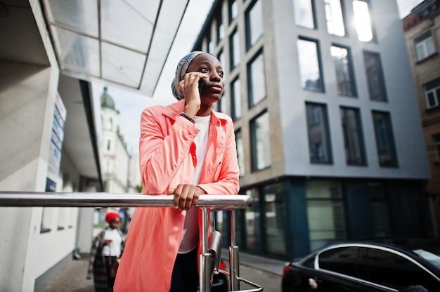 Jovem mulher moderna elegante, atraente, alta e magro em hijab falar no telefone móvel contra a cidade