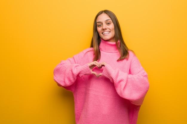 Jovem mulher moderna fazendo uma forma de coração com as mãos
