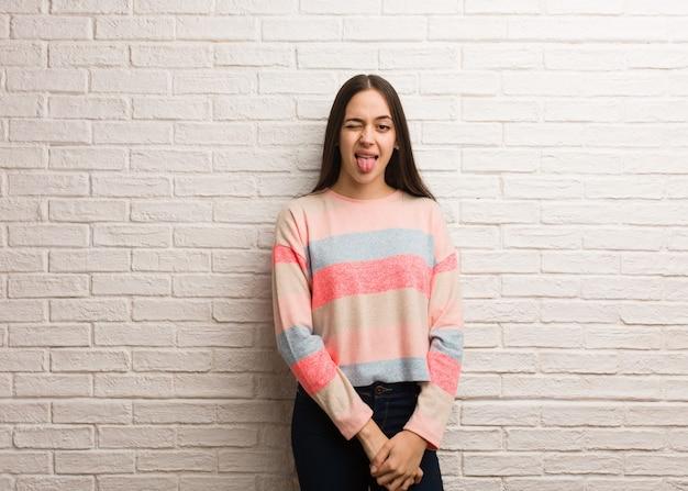 Jovem mulher moderna funnny e amigável mostrando a língua