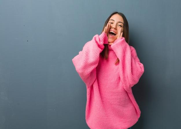 Jovem mulher moderna gritando algo feliz para a frente