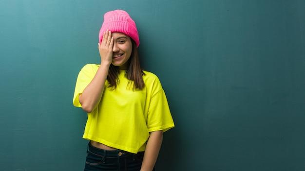 Jovem mulher moderna gritando feliz e cobrindo o rosto com a mão
