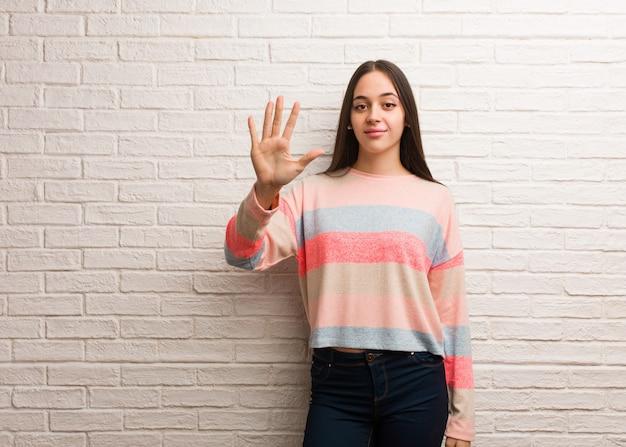 Jovem mulher moderna, mostrando o número cinco