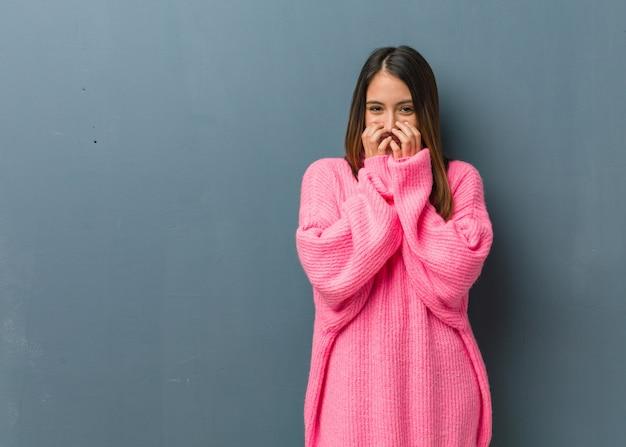 Jovem mulher moderna rindo de algo, cobrindo a boca com as mãos