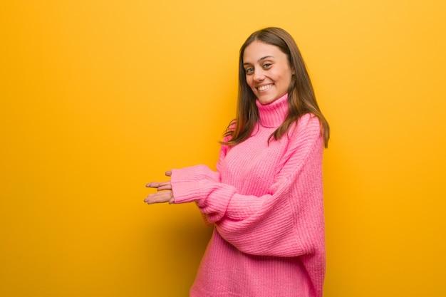 Jovem mulher moderna segurando algo com as mãos