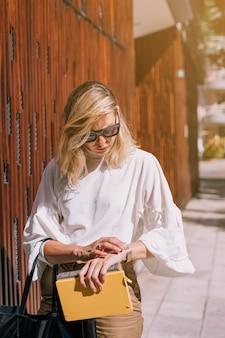 Jovem mulher moderna segurando livros na mão, olhando o tempo