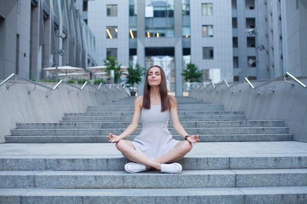 Jovem mulher moderna sentada em posição de lótus e meditando sobre o fundo urbano da cidade