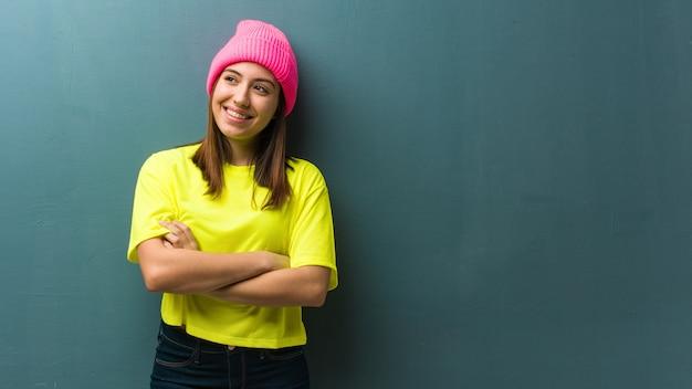 Jovem mulher moderna sorrindo confiante e cruzando os braços, olhando para cima