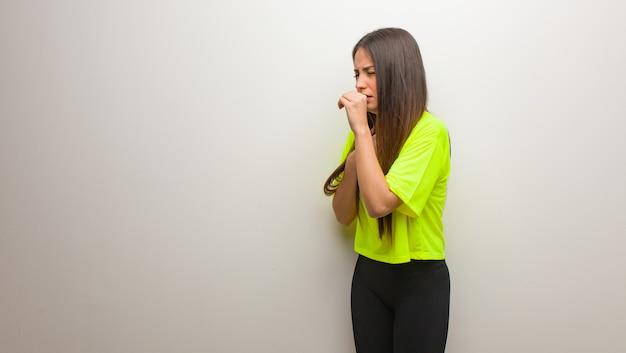 Jovem mulher moderna tossindo, doente devido a um vírus ou infecção