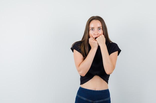 Jovem mulher mordendo os punhos emocionalmente em uma blusa preta