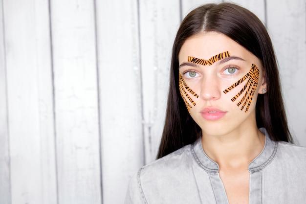 Jovem mulher morena atraente com tigre colorido fitas após a gravação do procedimento de rosto no salão de beleza