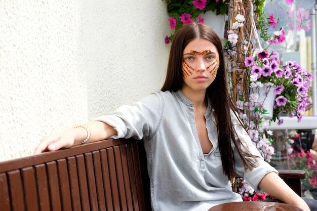 Jovem mulher morena atraente com tigre colorido fitas depois de gravar o procedimento de rosto no salão de beleza, sentado na rua
