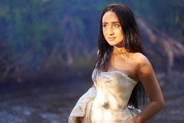 Jovem mulher morena bonita no vestido de casamento branco ao ar livre perto do rio com os cabelos molhados na noite a luz do sol no rosto