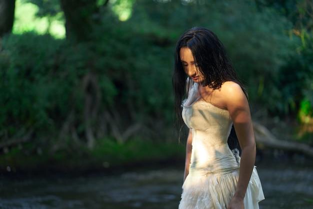 Jovem mulher morena bonita no vestido de casamento branco ao ar livre perto do rio com os cabelos molhados