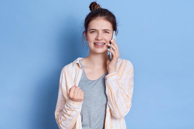 Jovem mulher morena conversa com um amigo e o punho cerrado, vestindo roupas casuais, em pé contra a parede azul.