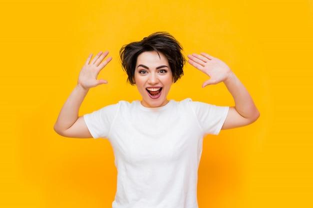 Jovem mulher morena feliz com um corte de cabelo curto em uma camiseta branca sobre um fundo amarelo. retrato de uma jovem mulher com várias emoções em um fundo amarelo. espaço para texto