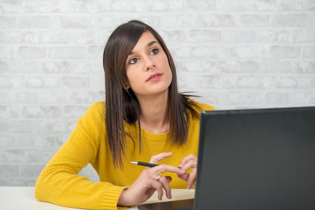 Jovem mulher morena pensativa no escritório