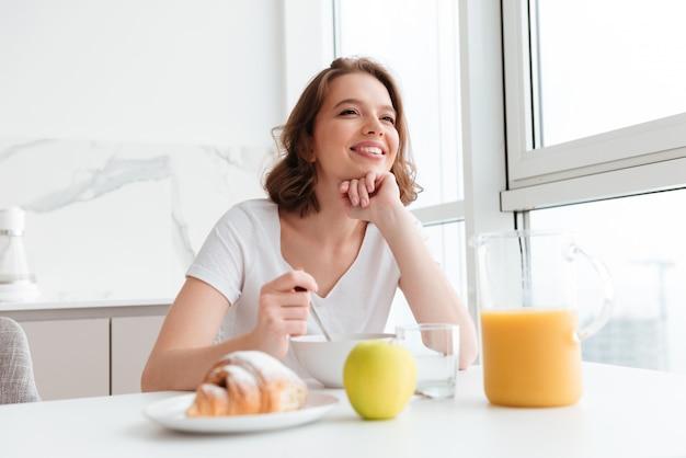 Jovem mulher morena sorridente em camiseta branca tomando café da manhã saudável enquanto localização na mesa da cozinha