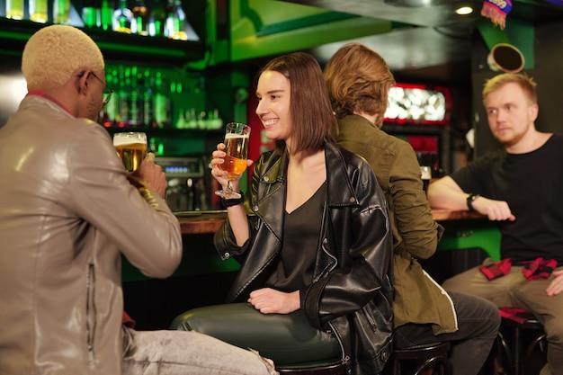 Jovem mulher morena sorridente em trajes casuais tomando cerveja no balcão do bar enquanto olha para o namorado na frente da câmera e fala com ele