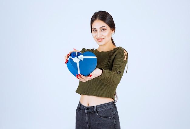 Jovem mulher mostrando a caixa de presente azul sobre fundo branco.