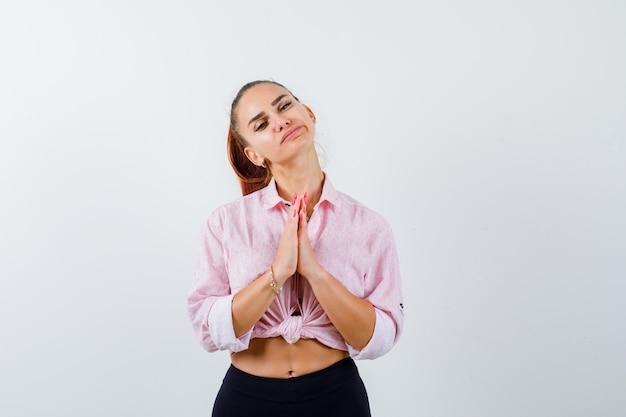 Jovem mulher mostrando as mãos postas em um gesto de súplica em uma camisa casual, calças e parecendo esperançosa Foto gratuita