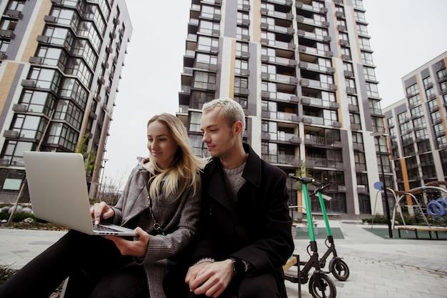 Jovem mulher mostrando fotos para seu amigo masculino e sorrindo. homem loiro sentado perto e olhando no laptop. eles se sentam em bancos perto de blocos de apartamentos. passando um bom tempo. duas e-scooters próximas.