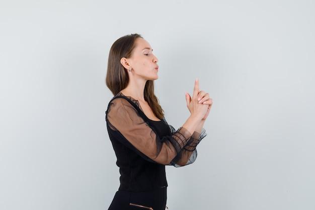 Jovem mulher mostrando gesto de arma em blusa preta e calça preta e olhando confiante, vista frontal.