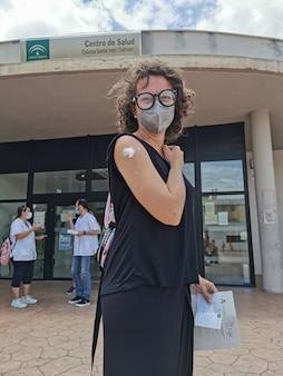 Jovem mulher mostrando o braço logo após receber a vacina macabra no centro de saúde