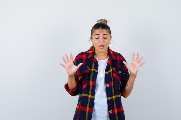 Jovem mulher mostrando o gesto de parada na camisa quadriculada e olhando chateada, vista frontal.