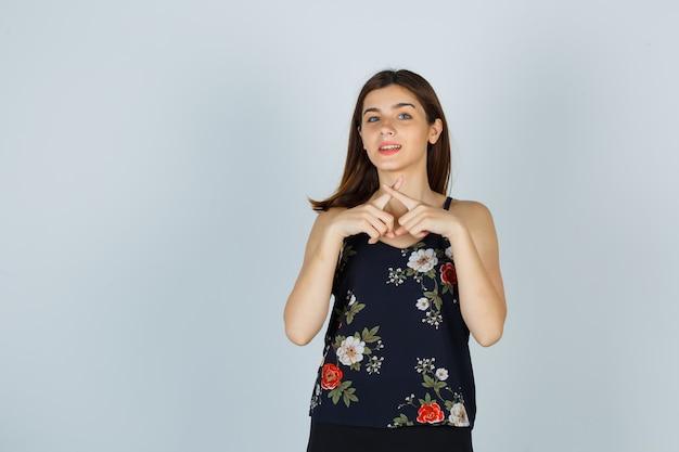 Jovem mulher mostrando o gesto de silêncio com os dedos cruzados, formando um x na blusa e olhando confiante, vista frontal.