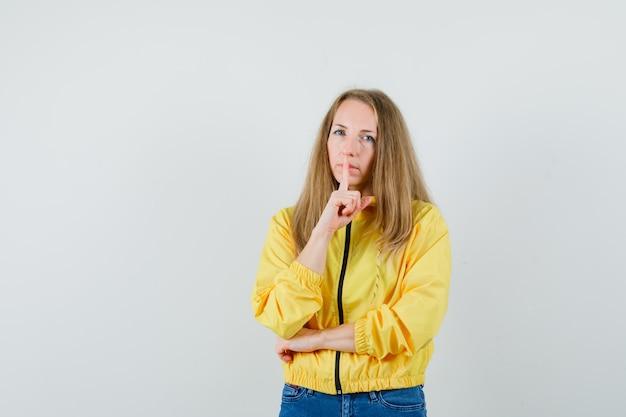 Jovem mulher mostrando o gesto de silêncio na jaqueta amarela e jeans azul e olhando sério, vista frontal.