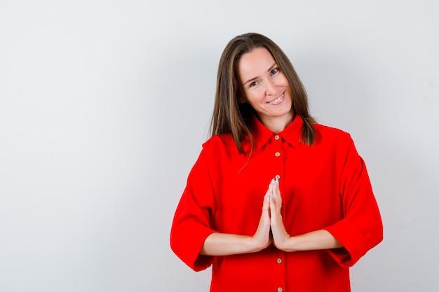 Jovem mulher mostrando o gesto namastê na blusa vermelha e olhando feliz, vista frontal.
