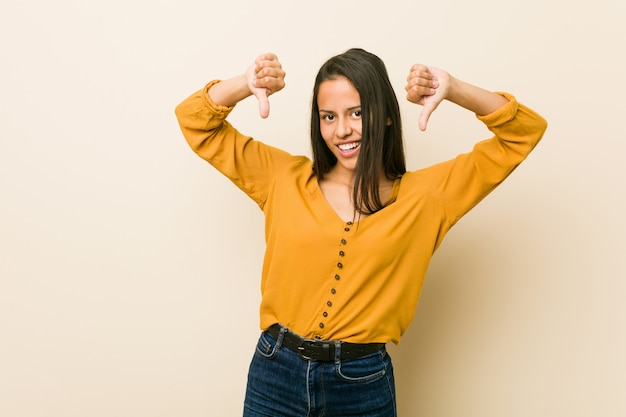 Jovem mulher mostrando o polegar para baixo e expressando antipatia